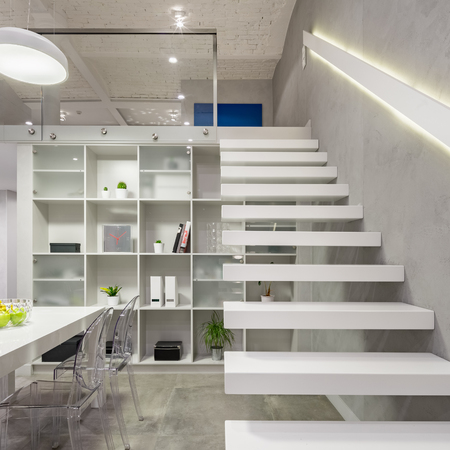 Loft apartment with white, modern, mezzanine stairs with led light in railing 免版税图像