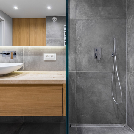 Gray bathroom with walk in shower, mirror and countertop basin