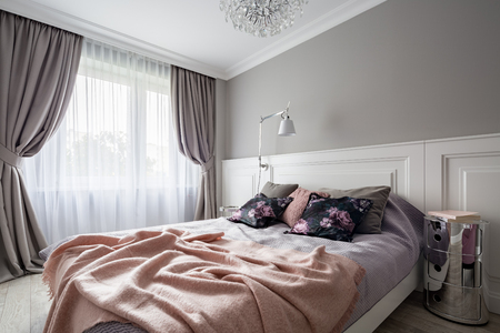 Pastel bedroom with double bed and decorative window curtains 免版税图像