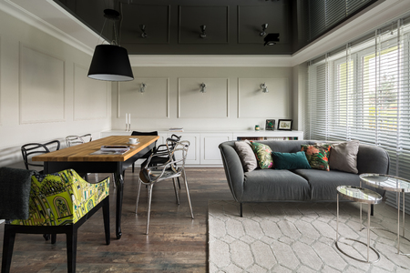 Living room with wooden dining table and floor and black stretch ceiling
