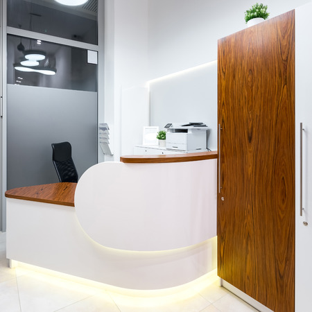 Bright and white office reception area with wooden desk Stock Photo