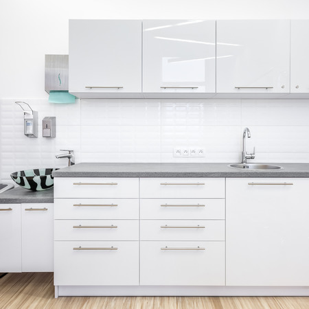 Clear, medical office with white cabinets and sink 版權商用圖片
