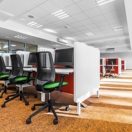 Moderna sala de computadoras con alfombra naranja moderna en el piso Foto de archivo