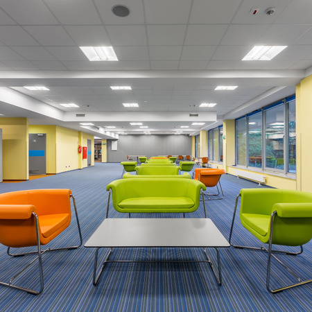 Modern office interior with colorful lounge area, with green and orange furniture