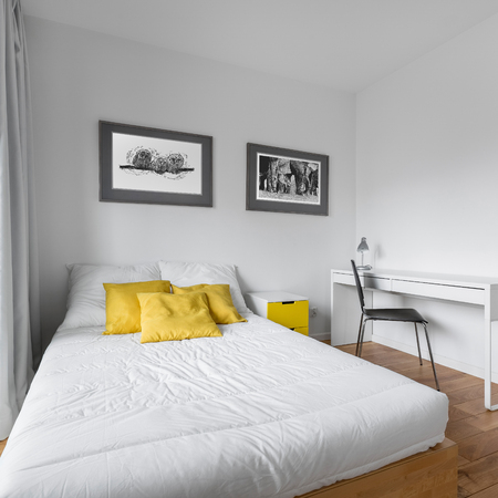 Cozy white bedroom with big twin-size bed and yellow accessories Stockfoto