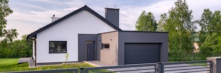 Vista panoramica di elegante villa con recinzione, garage e prato Archivio Fotografico