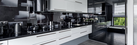 Contemporary black and white elegant kitchen with long worktop, panorama Stock Photo