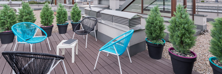 Beautiful rooftop terrace with modern black and turquoise chairs, panorama