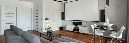 Living room with sofa, dining table, white chairs and projector screen, panorama