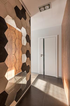 Home corridor with decorative octagonal mirror and white door