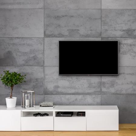 Appartamento con tv, mobile bianco e muro di cemento