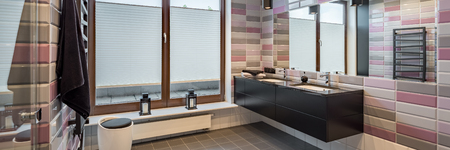 Panorama of spacious bathroom with brick tiles, black cabinet and two sinks 写真素材