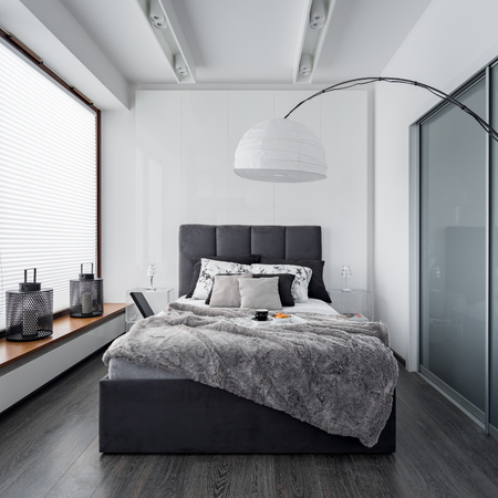 Modern bedroom with floor lamp, wardrobe and double bed