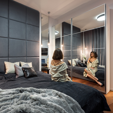 Beautiful woman sitting on bed in modern bedroom with double bed and mirrored wardrobe