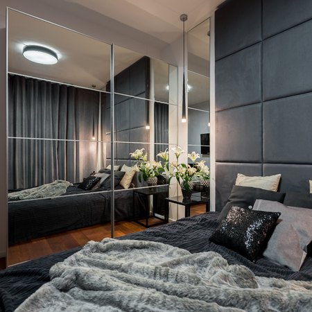 Contemporary bedroom with double bed and mirrored wardrobe