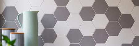 Keuken met grijze en witte honingraatmuurtegels en stijlvolle voedselcontainers, panorama