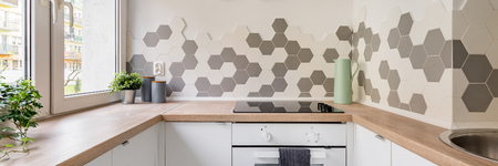 Panorama of kitchen in scandinavian style with white cabinets, wooden countertop and hexagonal wall tiles 版權商用圖片