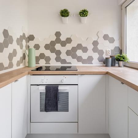 Keuken in Scandinavische stijl met witte kasten, houten aanrechtblad en zeshoekige wandtegels