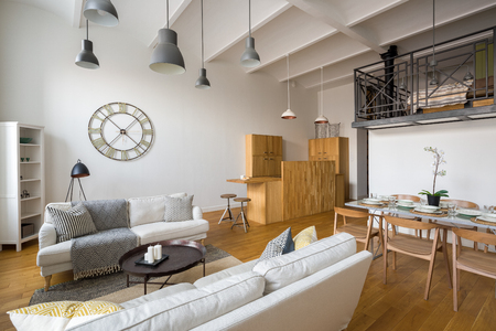 Multifunctional home interior with stylish ceiling beams and mezzanine Archivio Fotografico