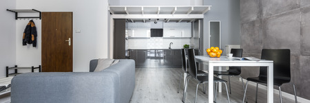 Panorama of modern, open plan apartment with dining table, black chairs and sofa Archivio Fotografico