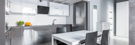Panorama of gray kitchen with white dining table and black chairs