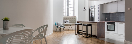 Panorama of modern apartment with open kitchen and round table Archivio Fotografico