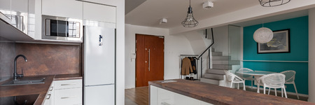 Panorama of contemporary home interior with kitchen open to dining area