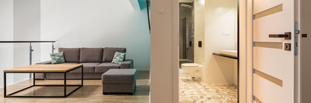 Panorama of modern living room with wooden table and open door to bathroom Archivio Fotografico