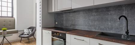 Panorama of modern kitchen with black basin and granite worktop
