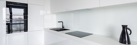 Panorama of white contemporary kitchen with black accessories