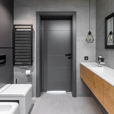 Cubic toilet and wooden cabinets in modern, gray bathroom Archivio Fotografico