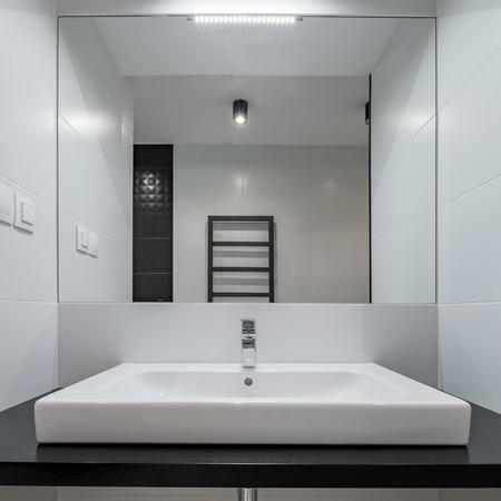 Monochromatic bathroom with black countertop, white basin and mirror