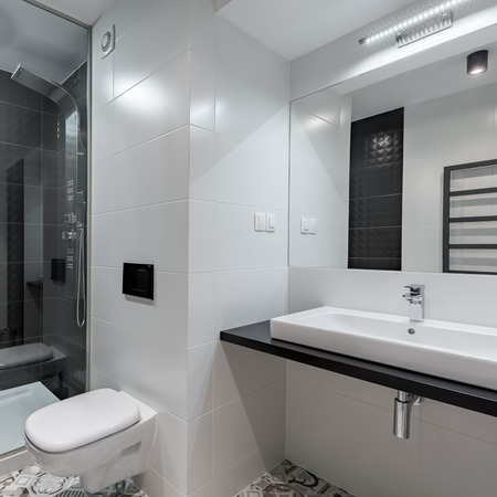 Classic bathroom interior with white tiling, basin and toilet