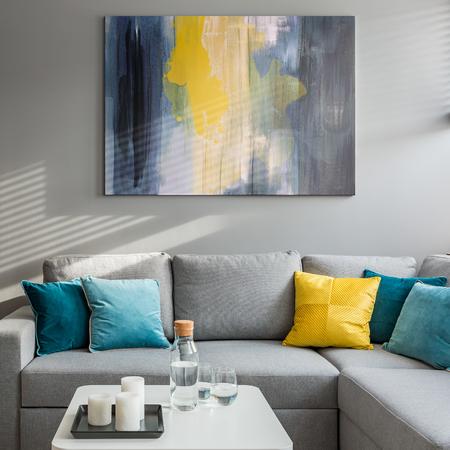 Sala de estar con sofá de esquina, cojines de colores y mesa de centro blanca. Foto de archivo