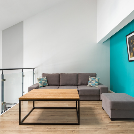 Living room with sofa, pouf, wooden table and turquoise wall Archivio Fotografico