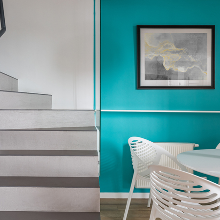 Home interior with stairs, turquoise wall and white chairs