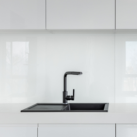 High gloss cabinets, countertop and black composite kitchen sink Stockfoto
