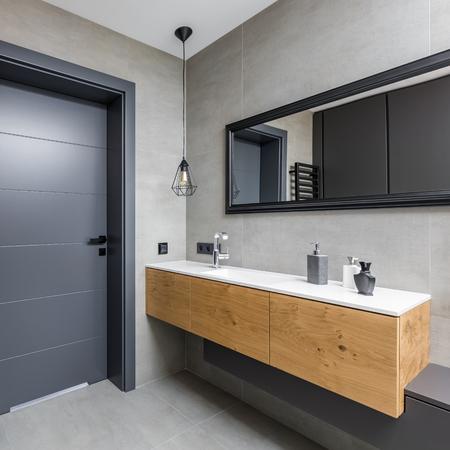 Dark bathroom with countertop basin, wooden cabinet and mirror