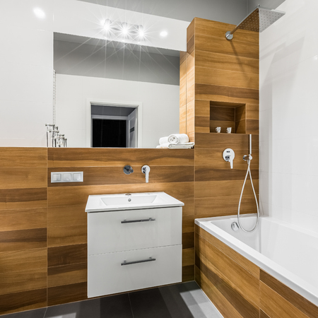 Modern bathroom with mirror, basin and wood effect tiles