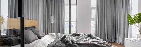 Panorama del interior del dormitorio de lujo con cama doble y cortinas grises