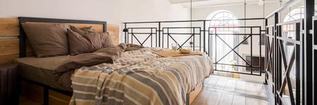 Panorama di una semplice camera da letto soppalcata con letto matrimoniale
