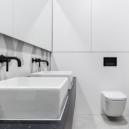White bathroom with two basins, cubic toilet and black details