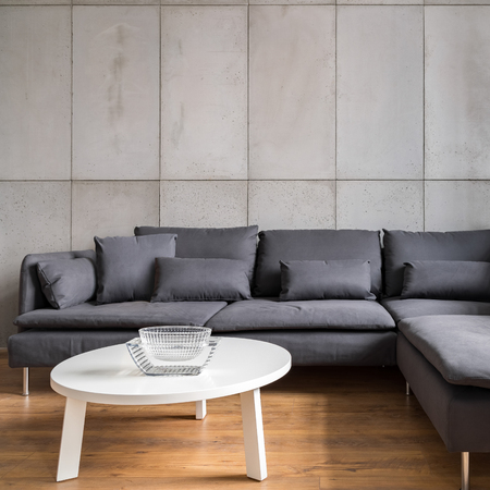 Home interior with concrete wall and big gray corner sofa
