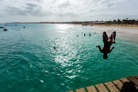 Boy is jumping from wooden pier into blue ocean Stock Photo