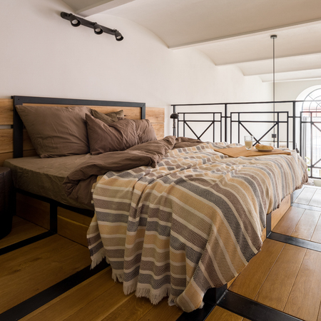 Stylish and comfortable mezzanine bedroom with wooden double bed