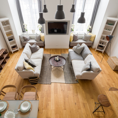 Top view of beautiful living room with hardwood flooring, big windows and stylish ceiling lamps
