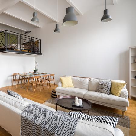 Elegante soggiorno con due divani, tavolo da pranzo e soppalco