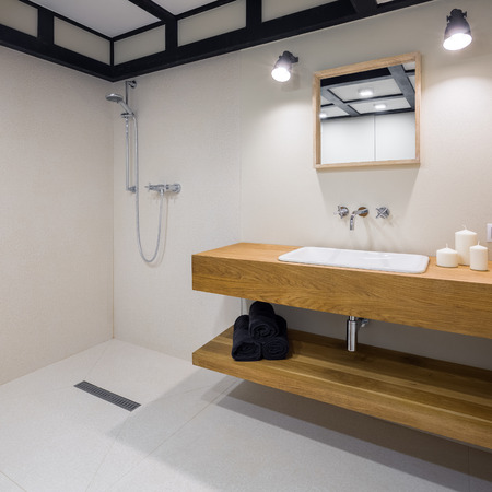 Minimalist bathroom with long, wooden countertop and open shower