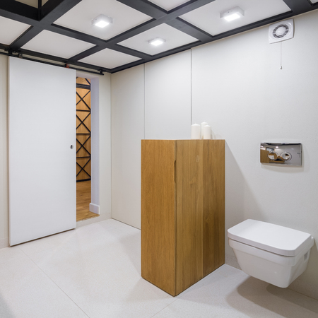 White bathroom with wooden furniture and coffered ceiling Imagens