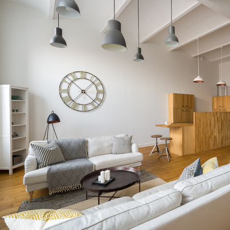 Cozy living room with functional wooden kitchenette and industrial lamps Archivio Fotografico